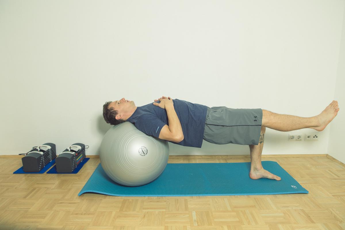 Gymnastikball Übungen Beine strecken in Rückenlage auf dem Ball
